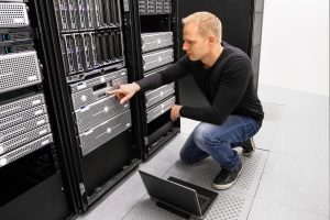 IT consultant working with laptop in datacenter