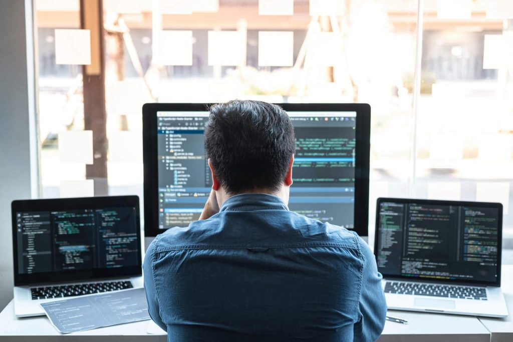 man with multiple computer screens